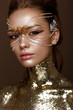 Beautiful girl in a golden mask and bright evening make-up. Beauty face. Photo taken in studio