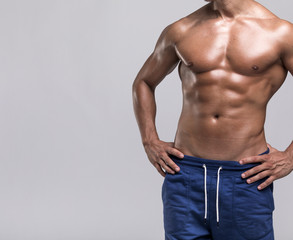 Fit man with muscular torso on grey background