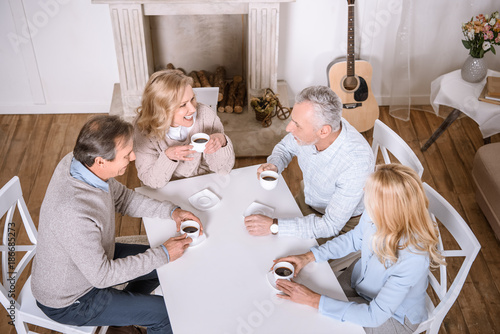 overhead view of friends sitting with tea at table at room interior