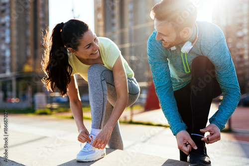Runners tying running shoes and getting ready to run - 186687027