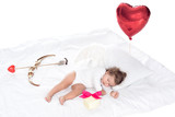 little cherub with wings lying on bed with heart balloon, present, bow and arrow, isolated on white - 186687604
