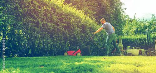 Foto Murales Mann mit rasenmäher im eigenen garten (Gartenpflege)