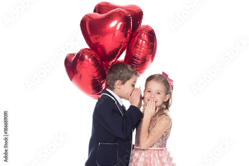 Foto Murales stylish little boy holding heart shaped balloons and whispering to smiling beautiful little girl isolated on white