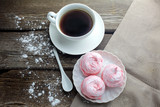 white ceramic cup with black coffee and marshmallow dessert on wooden table, top view