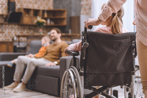 cropped shot of mother holding wheelchair with little daughter while father and son sitting on sofa behind