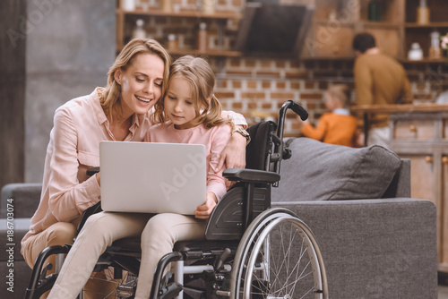 smiling mother and little daughter in wheelchair using laptop together at home