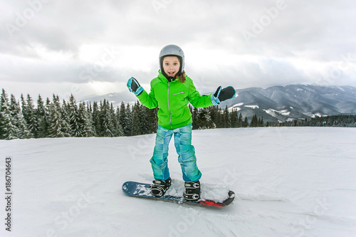 obraz lub plakat Cute child girl is snowboarding on the snow mountain