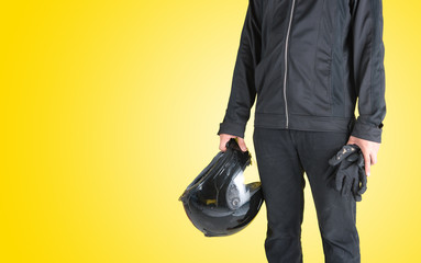 Biker with holding motorcycle helmet on yellow background,Text Space