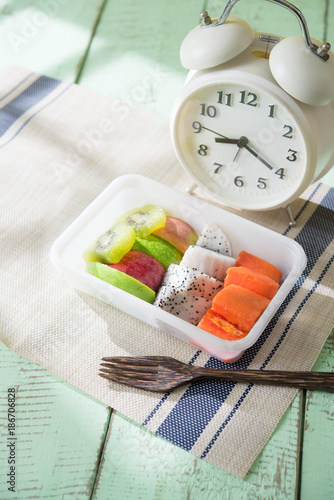 Foto Murales Mix sliced fruits (papaya,dragon fruit,apple, kiwi) and alarm clock on rustic wooden background