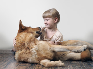 A small child deals with a huge dog