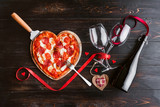 a festive dinner of pizza in the shape of a heart and a bottle of wine. - 186719853