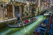 Gondolas carry tourists on the canal, Venice, Italy. Canals and historic buildings of Venice, Italy. Narrow canals, old houses, reflection on water on a summer day in  Venice, Italy.