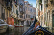 Canals and historic buildings of Venice, Italy, from gondola. Narrow canals, old houses, reflection on water on a summer day in  Venice, Italy.