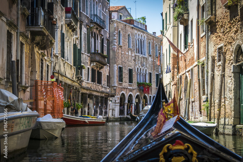 Venice Canals and historic buildings of Venice, Italy, from gondola. Narrow canals, old houses, reflection on water on a summer day in Venice, Italy.