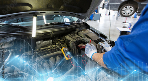 auto mechanic man with multimeter testing battery - 186734443