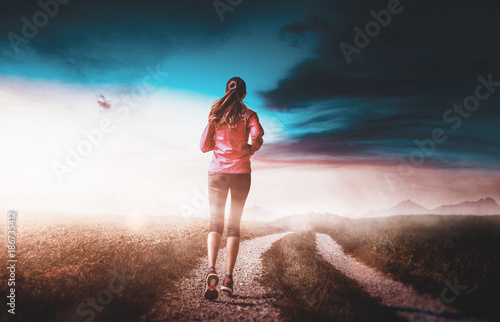 Woman jogging along a dirt road in countryside