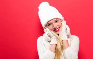 Happy young woman in winter clothes on a solid background