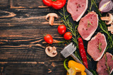 Beef steak with fresh vegetables and rosemary and spices on a black wooden background. Top view. Free space for text. - 186749668