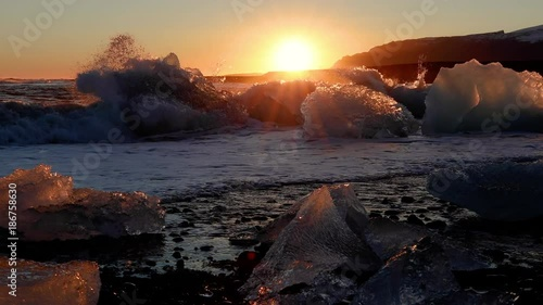 Small icebergs on the shore of a black sand beach in Iceland at sunset.