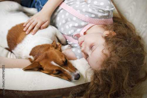 Little girl embracing a puppy dog. - 186764252