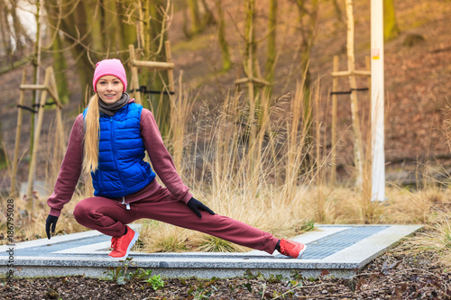 Poster Woman wearing sportswear exercising outside during autumn
