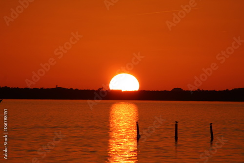 Fotobehang Rood traf. Vibrant orange sunset with sun dipping into the horizon