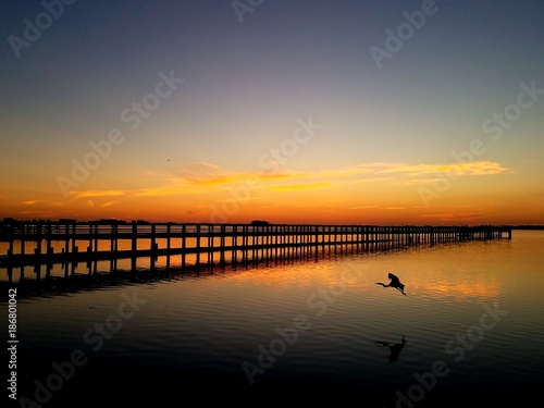 Keuken foto achterwand Zee zonsondergang Low clouds after sunset over a fishing pier with water reflection
