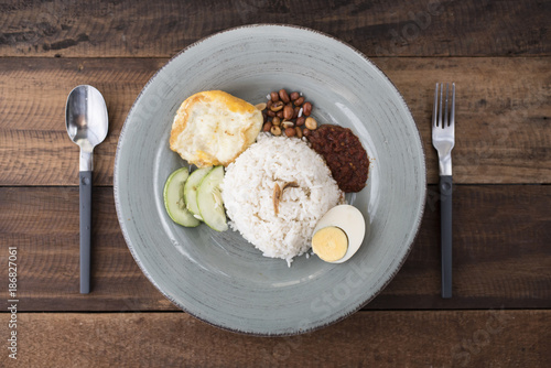 Foto Murales malaysian food/cuisine (nasi lemak) - white rice with fried egg,anchovies,spicy sauce (sambal) and peanuts all put together in a plate on a wooden bakground.