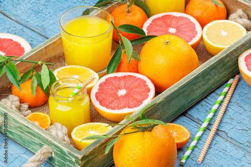Different fruits and glass with fresh orange juice - 186831041