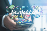 Concept of man holding futuristic interface with newsletter title and multimedia icons flying all around - Internet concept - 186832038