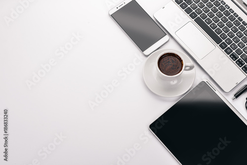 White Office Desk. Laptop, phone, cup of coffee, glasses, pen, pencil. On a white background. Top view. Free space for text.
