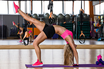 Sporty muscular woman is making stretching in gymnastic hall