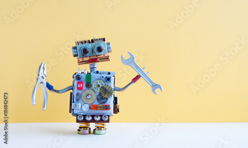 Friendly robot serviceman pliers hand wrench. Fixing maintenance concept. Creative design toy, cogs wheels gears silver metallic body. Yellow background. Copy space