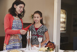 Jewish mother and daughter lighting candles for Shabbat meal - 186844203