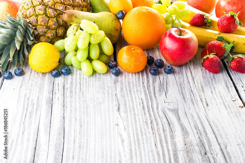 Foto Murales Fresh fruits on wooden background