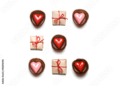Foto Murales Minimal styled Valentine's Day flat lay top view isolated on white background. Gifts and chocolate heart-shaped candies in geometric rows. Copy space. Love concept. St Valentine's pattern