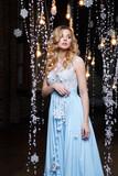 Beautiful blonde girl in a long blue dress on a dark background. - 186846679