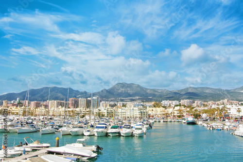 Benalmadena Puerto Marina sport port, a view to piers with white modern luxury sport yachts, Mediterranean sea and mountains and cloudy sky at the background. Spain winter relax vacation concept.