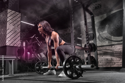 Young beautiful muscular girl sportsman bodybuilder doing exercises in a modern gym using a barbell, against a dark background. - 186860663