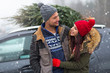 Couple with their christmas tree on roof of the car