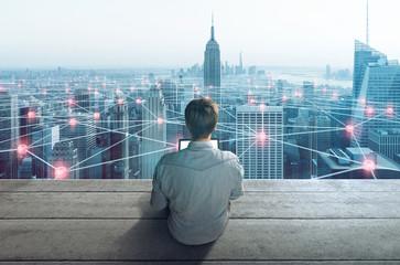 Mann mit Notebook vor großer Stadt