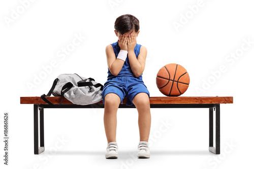 Fotobehang Basketbal Sad little basketball player sitting on a bench