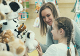 Woman and her daughter choosing toy in kids store. - 186871812