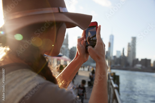 Wall mural Tourist Taking Photo Of Manhattan Skyline On Mobile Phone