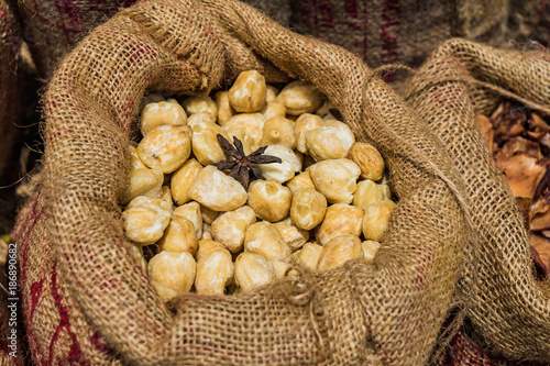 Sack of Dried Siam Cardamom on wooden background