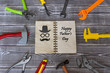 Congratulations Happy Fathers Day old notebook is surrounded by a toy tool on a rustic background. Black hat symbol with glasses and mustache. Best gifts to your beloved father.