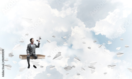 Foto Murales Businessman announcing something in loudspeaker and paper planes fly around