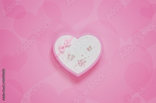 Gift box in the form of a heart on a pink paper background. The concept for the Valentine's Day, wedding, engagement and other romantic events. Top view, close-up. - 186900618