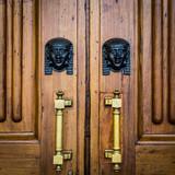 Sphinx heads entrance on wooden door