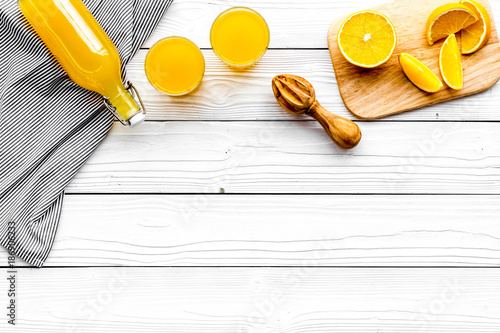 Make orange juice. Juicer, beverage in bottle and glasses near slices of oranges on white wooden background top view copyspace